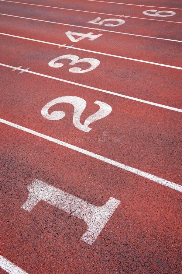 Athletische Laufbahn nummeriert Wege lizenzfreie stockfotos