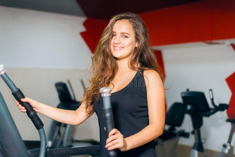 Athletische Mädchenzüge auf dem Steppersimulator Frau im Turnhallenlächeln stockbild