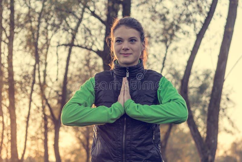 Athletische weibliche übende Balance bei der Stellung zwischen Bäumen stockbilder