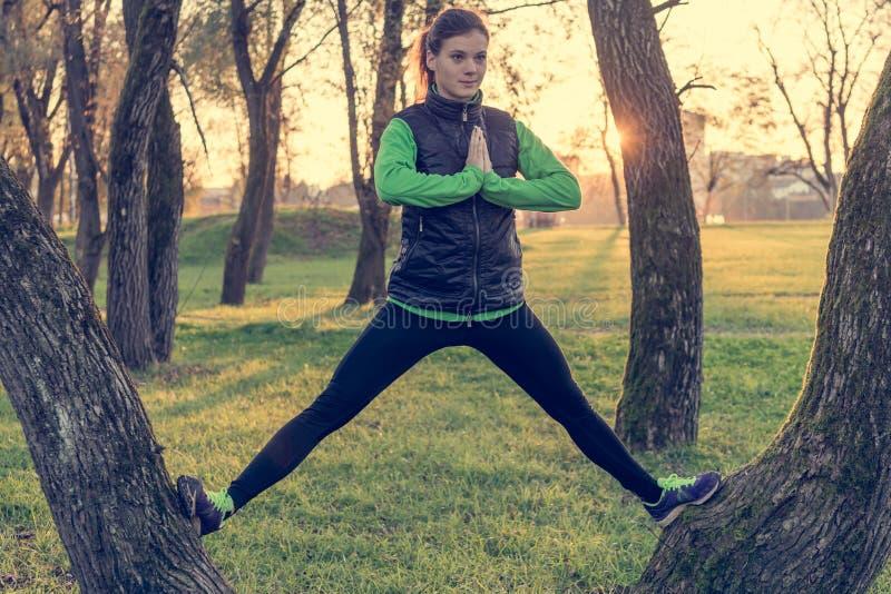 Athletische weibliche übende Balance bei der Stellung zwischen Bäumen stockfoto