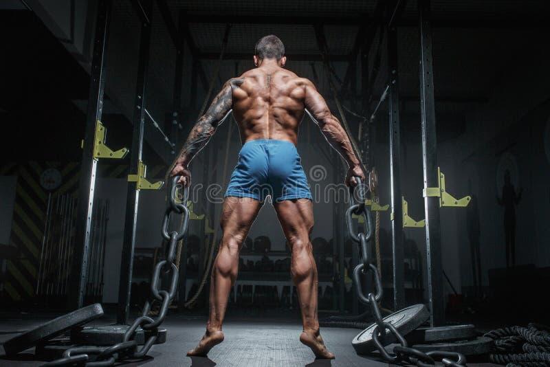 Athletischer Bodybuilder des gepumpten Mannes mit Kette in der Turnhalle Rückseitige Ansicht stockfoto