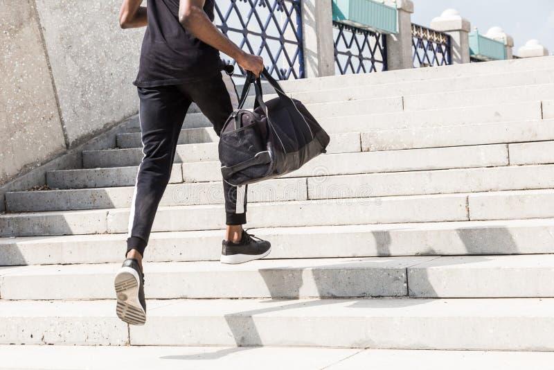 Athletischer junger afroer-amerikanisch Mann, der auf der Promenade läuft Schwarzer männlicher Läufer, der draußen sprintet Gesun stockbild