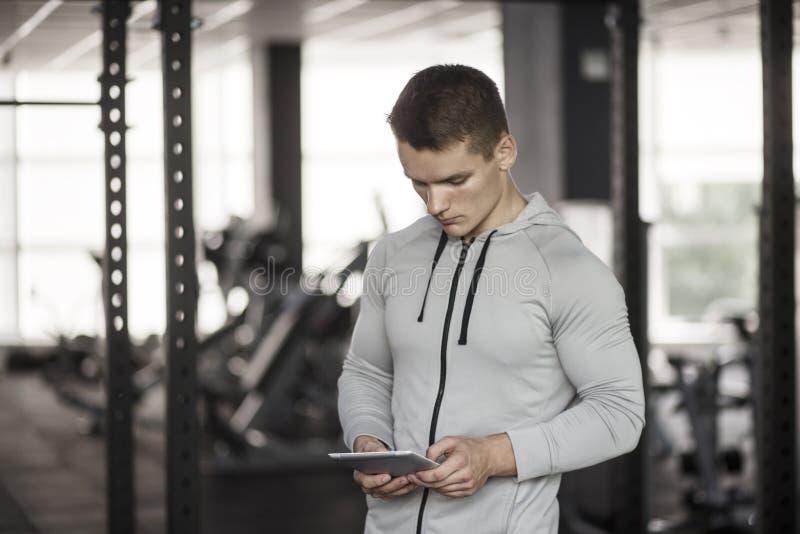 Athletischer junger Mann auf digitaler Tablette vor der Ausbildung an der Turnhalle, unter Verwendung der Anwendung mit Trainings stockfoto
