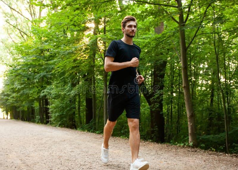 Athletischer junger Mann, der in die Natur läuft Porträt des männlichen Läufertrainings für Marathon Gesunder Lebensstil stockfotografie