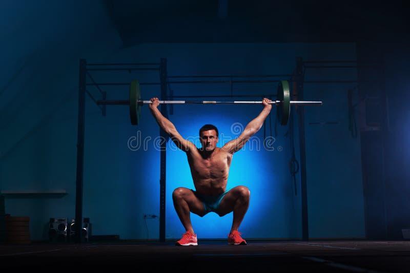 Athletischer junger Mann, der mit Barbell in der Turnhalle ausarbeitet lizenzfreies stockbild