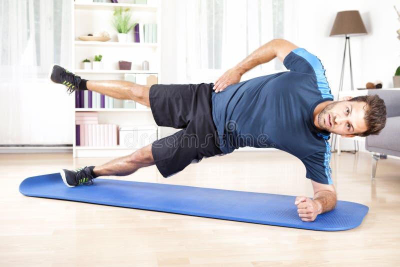 Athletischer Mann in den Seitendielen mit einem Bein angehoben stockbild