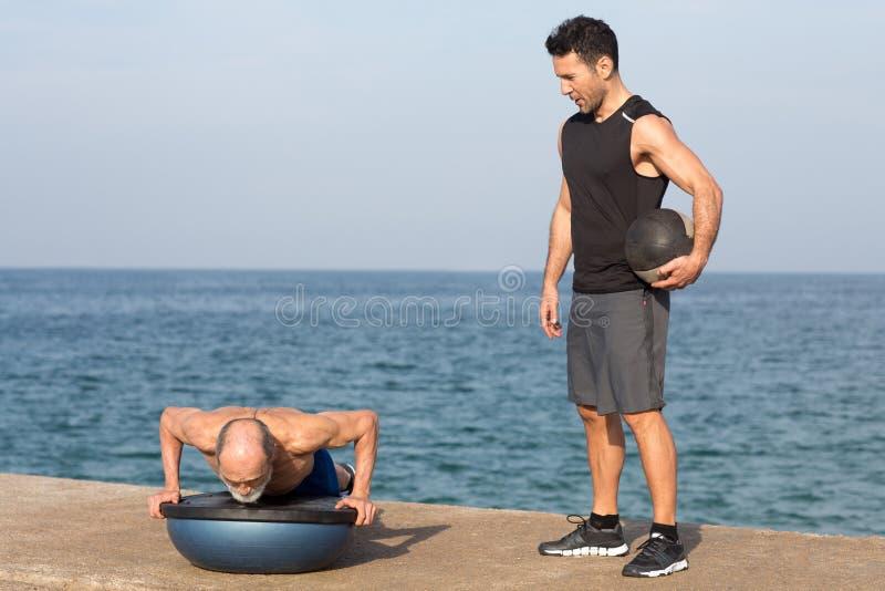 Athletischer Mann, der eine Liegestützübung mit Trainer auf Balancenplattform macht lizenzfreie stockbilder