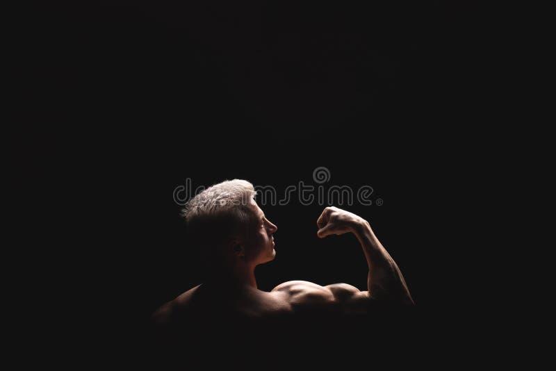 Athletischer Mann der hübschen Energie im drastischen Licht Starker Bodybuilder mit perfekten Schultern, Bizeps, Trizeps, Rücksei stockbild