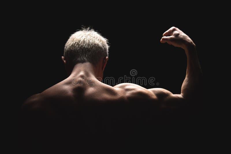 Athletischer Mann der hübschen Energie im drastischen Licht Starker Bodybuilder mit perfekten Schultern, Bizeps, Trizeps, Rücksei stockfotografie