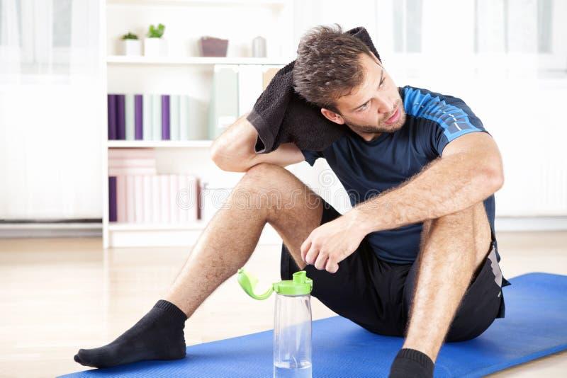 Athletischer Mann, der nach seiner Innenübung stillsteht lizenzfreie stockfotografie