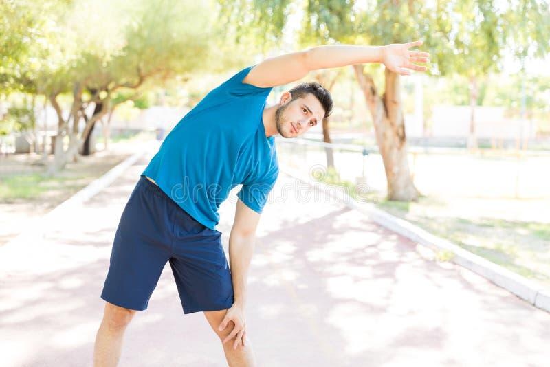 Athletischer Mann, der rechte Körperhälfte im Park ausdehnt stockbild