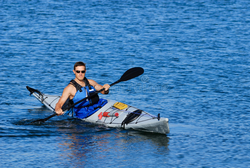 Athletischer Mann, der weg im Seekajak zeigt stockfotos