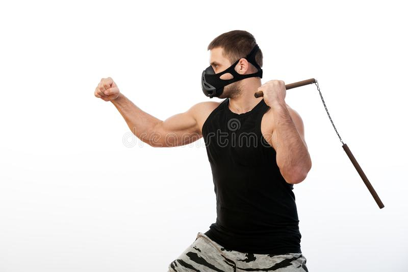 Athletischer Mann mit nunchaks lizenzfreie stockfotografie