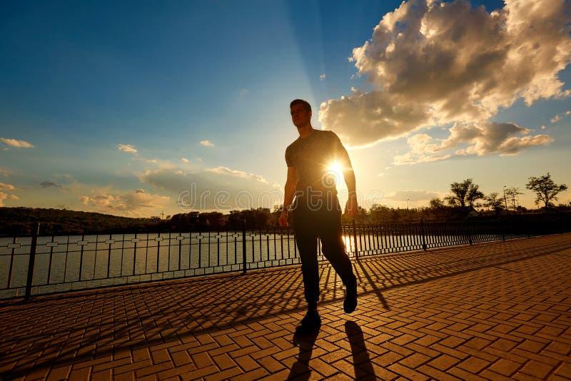 Athletischer Mann nachdem dem Rütteln in den Strahlen der Abendsonne sport stockbilder