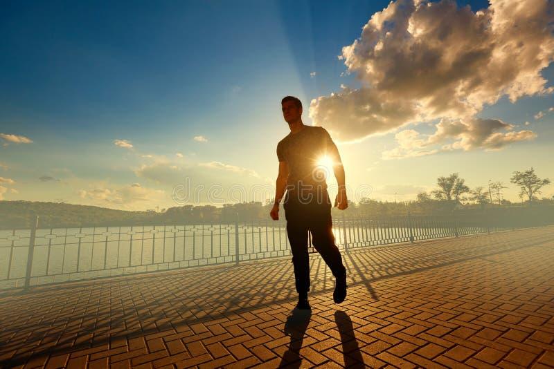Athletischer Mann nachdem dem Rütteln in den Strahlen der Abendsonne sport stockfotografie