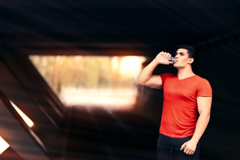 Athletischer Mann-Trinkwasser und Stillstehen vom Eignungs-Programm stockbilder