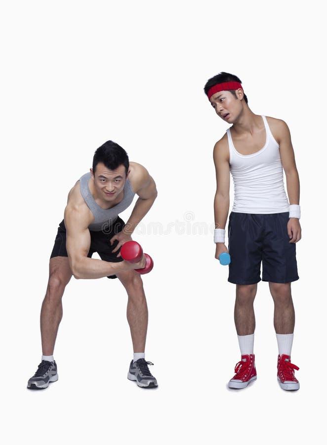 athletischer Mann- und Trainingsanfänger, der Muskeln, Gegenteil, Atelieraufnahme zeigt stockfotos