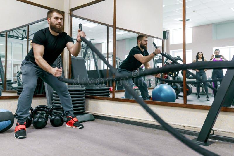 Athletischer muskulöser bärtiger Mann, der in der Turnhalle mit Kampfseilen trainiert Sport, Training, Leute, gesundes Lebensstil stockbilder
