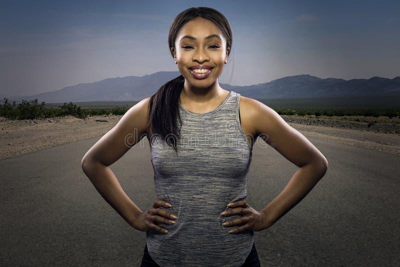Athletischer schwarzer weiblicher Läufer, der vor einer Straße aufwirft lizenzfreies stockfoto
