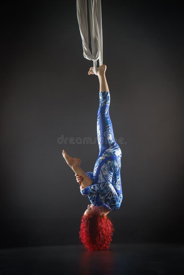 Athletischer sexy Luftzirkuskünstler mit Rothaarigen im blauen Kostüm, das Tricks auf der Luftseide macht lizenzfreies stockbild