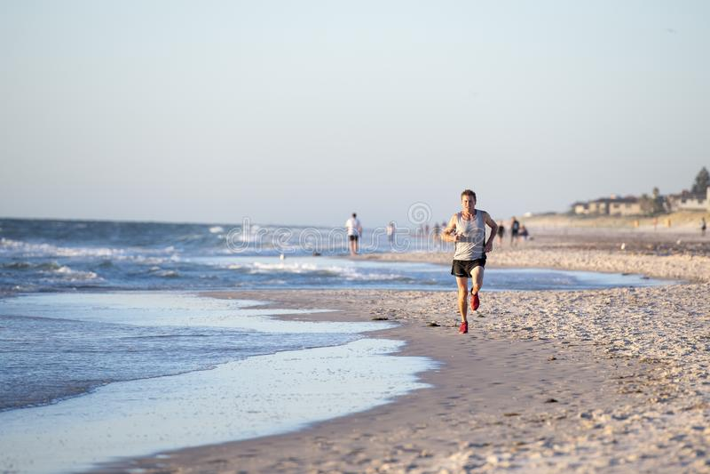 Athletischer Sitz und starker Läufer bemannen Training auf Sommersonnenuntergangstrand im Seeuferbetrieb und im Eignungstraining  lizenzfreie stockfotografie
