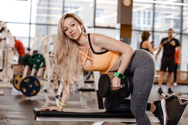 Athletisches blondes M?dchen mit dem langen Haar, das in einer Sportkleidung gekleidet wird, tut ?bung auf der Bank mit Dummk?pfe stockfotografie