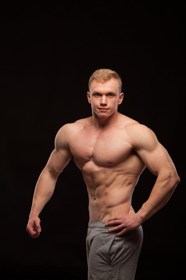 Athletisches Eignungmodell des gutaussehenden Mannes, das sechs Satz-ABS und schiefe Bauchmuskeln zeigt Getrennt auf schwarzem Hi stockbilder