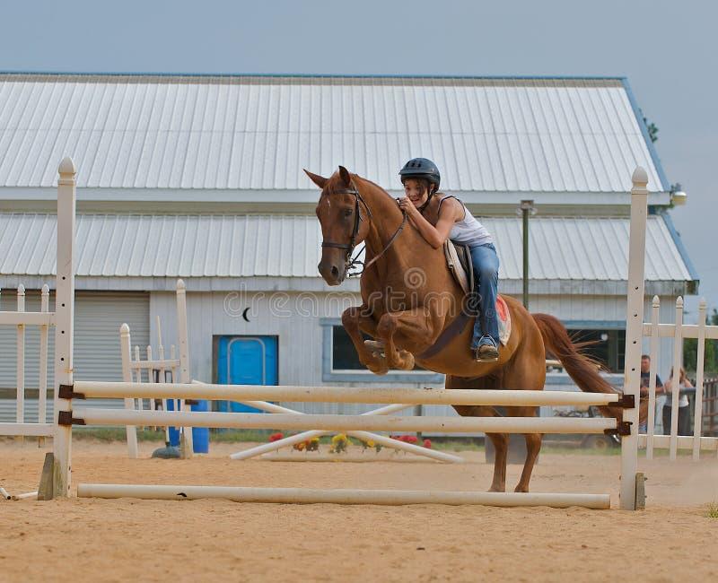 Athletisches jugendlich Mädchen, das ein Pferd über Schienen springt. lizenzfreie stockfotografie