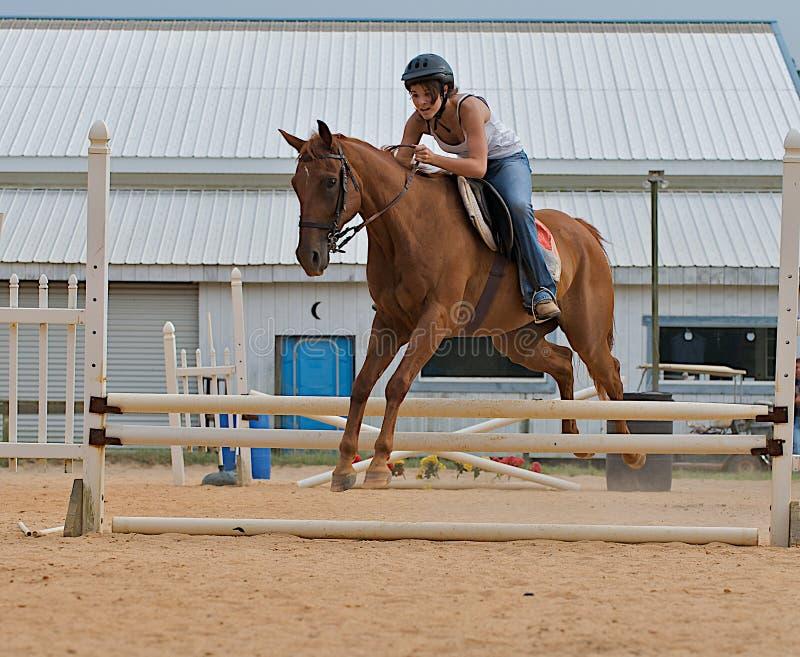 Athletisches jugendlich Mädchen, das ein Pferd über Schienen springt. lizenzfreies stockbild