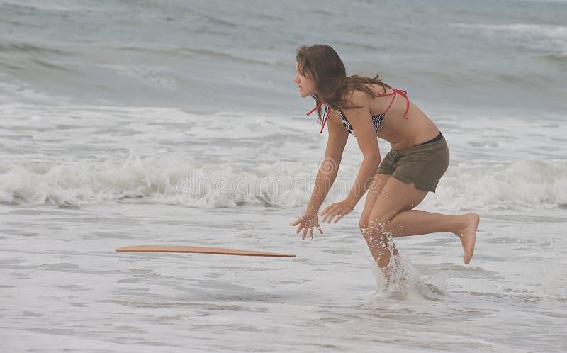 Athletisches jugendlich Mädchen, das einen Vorstand in den Ozean wirft stockfoto