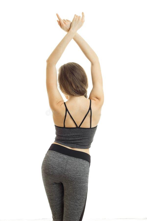 Athletisches junges Mädchen in der grauen Hose und Spitzen wert das Drehen Ihr zurück zu der Kamera Hände oben halten lizenzfreies stockbild