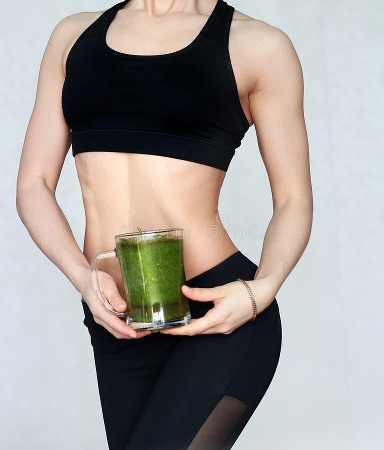 Athletisches Mädchen, das einen grünen Smoothie hält Trinkendes grünes Konzept eines gesunden Cocktails stockfoto