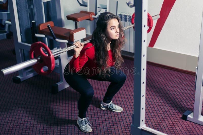 Athletisches Mädchen duckt sich mit einem Barbell Schönheit, die körperliche Bewegungen in der Turnhalle tut Sportgewichtheben stockfotografie