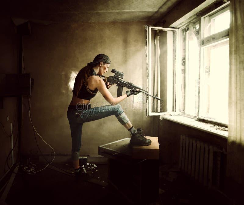 Atirador furtivo e soldado da mulher que apontam o rifle na janela imagem de stock royalty free