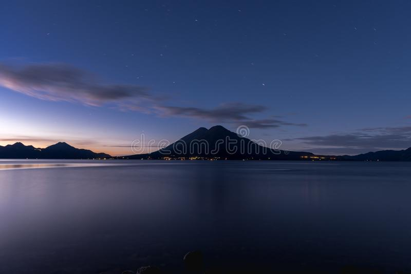 Atitlan Lake in Guatemala. Long Exposure Night Photo Shoot. Volcano in Background. Panning Stars in the Sky. Lights Reflection on royalty free stock photo