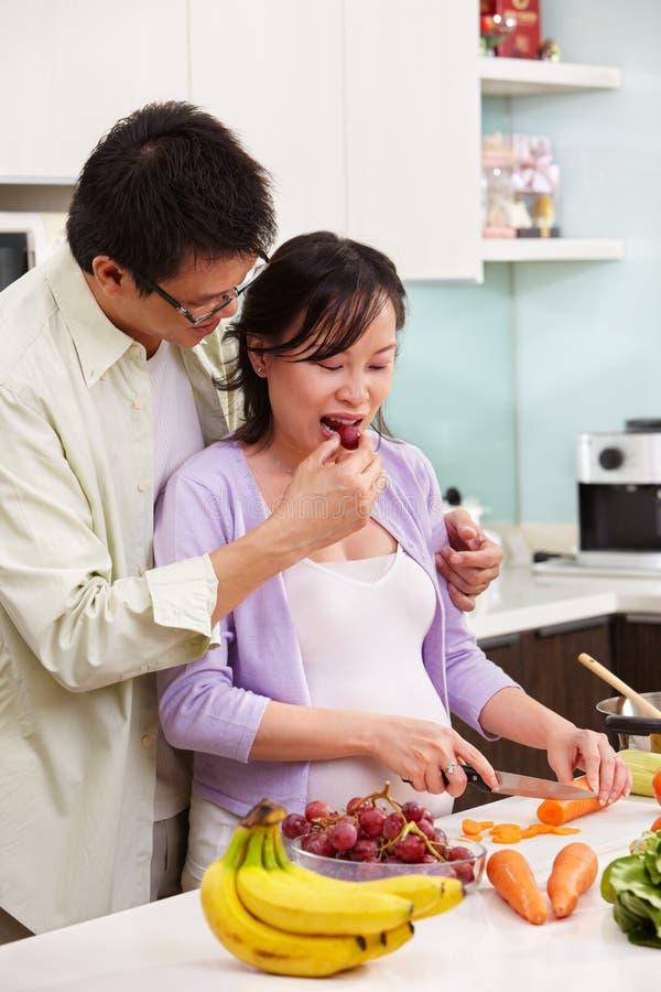 Atividade asiática dos pares na cozinha foto de stock