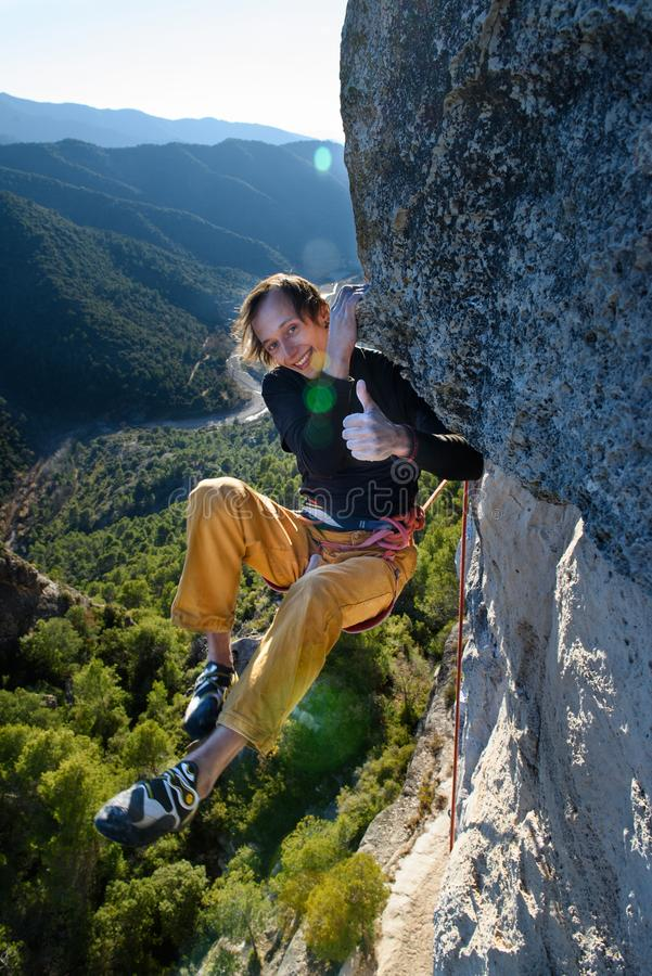 Atividade do esporte exterior Montanhista de rocha feliz que ascensão um penhasco desafiante Escalada extrema do esporte imagens de stock royalty free