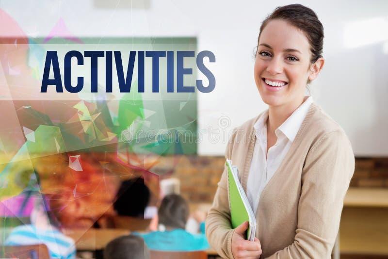 Atividades contra o professor bonito que sorri na câmera na parte traseira da sala de aula fotos de stock