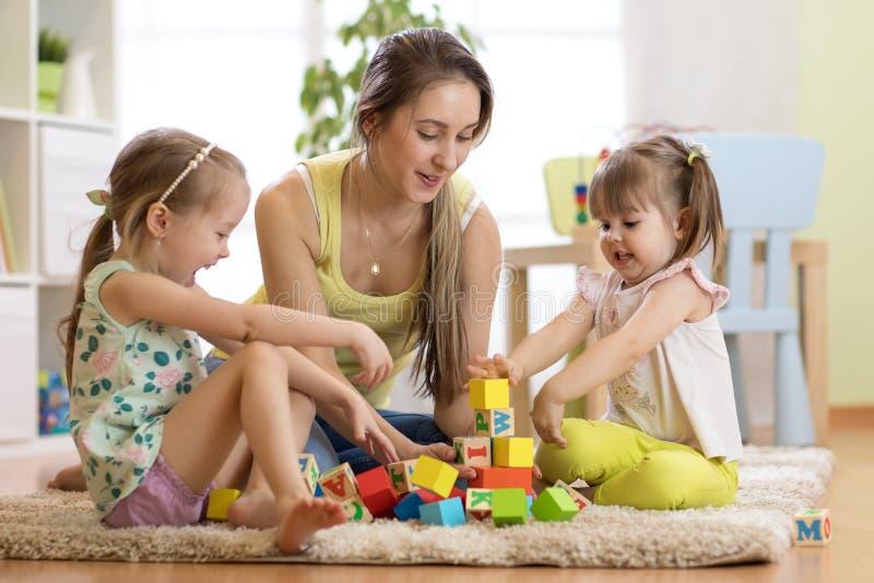 Atividades da família na sala de crianças Sira de mãe e suas crianças que sentam-se no jogo do foor imagem de stock royalty free