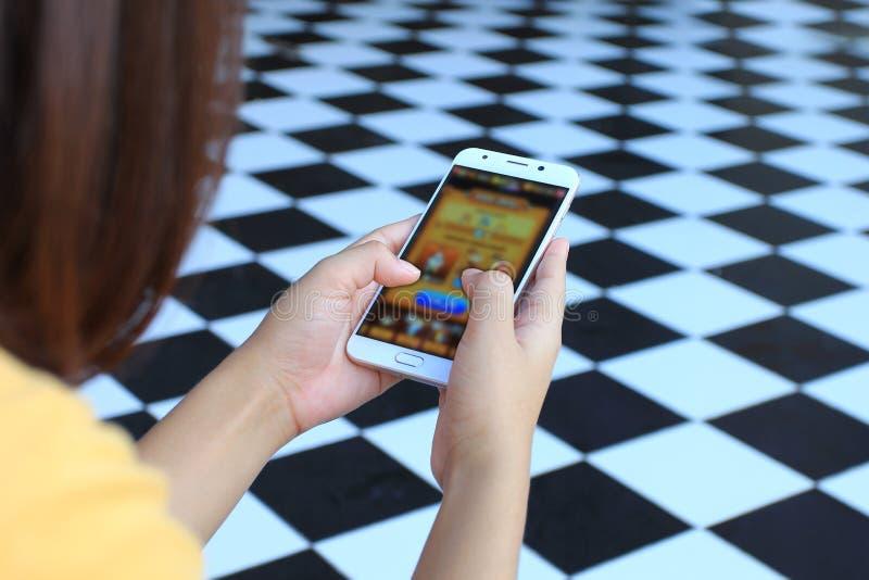 Atividades da jovem mulher que jogam jogos de vídeo no smartphone, na educação e no Internet das coisas IoT fotos de stock