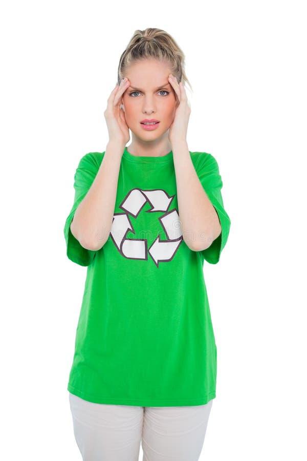 Ativista ambiental olhando de sobrancelhas franzidas que veste reciclando o levantamento do tshirt imagem de stock