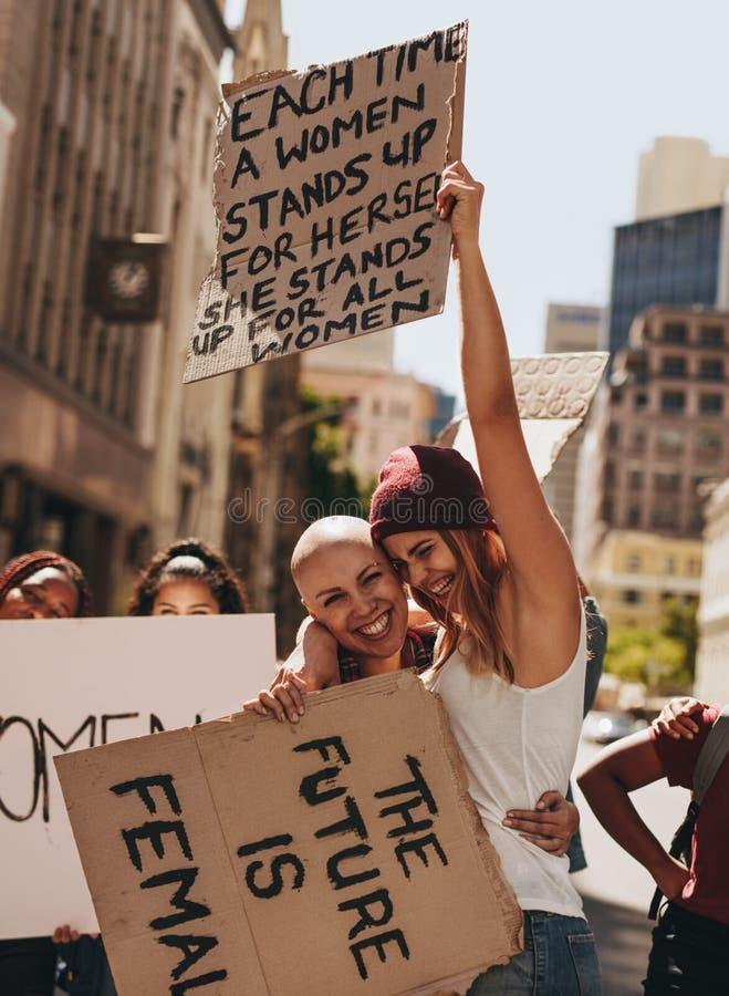 Ativistas novos felizes que protestam com quadros indicadores fotografia de stock royalty free