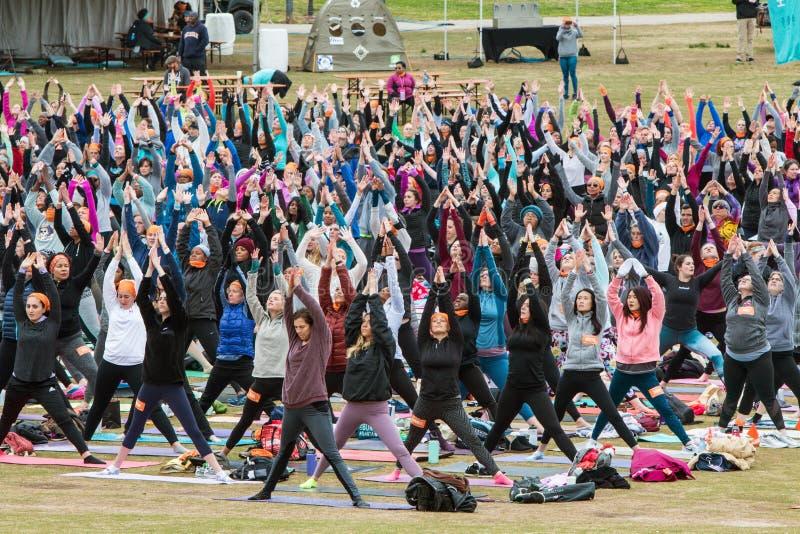 People Do Upward Salute Pose In Large Outdoor Yoga Class. Atlanta, GA, USA - April 8, 2018: Dozens of people do version of upward salute pose as they take part royalty free stock photos