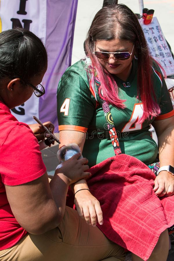 Female Gets Star Airbrushed Onto Arm At College Football Festival. Atlanta, GA, USA - August 25, 2018:  A female wearing a University of Miami football jersey royalty free stock photography
