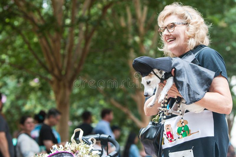 Woman Carries Dog Wearing Darth Vader Costume At Doggy Con. Atlanta, GA, USA - August 18, 2018: A woman carries a small dog dressed like Darth Vader from Star stock photography