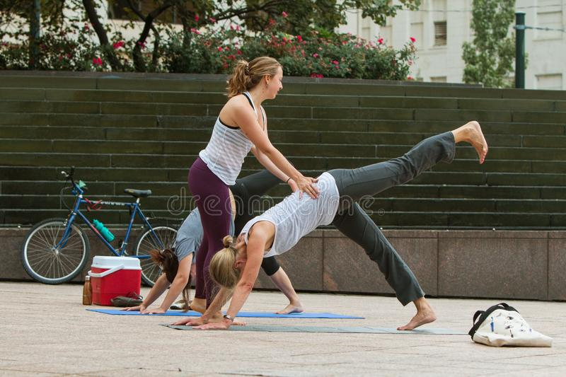 Yoga Instructor Teaches Women At Free Class In Public Park. Atlanta, GA, USA - August 18, 2018: A young female yoga instructor teaches yoga positions to women in royalty free stock photography