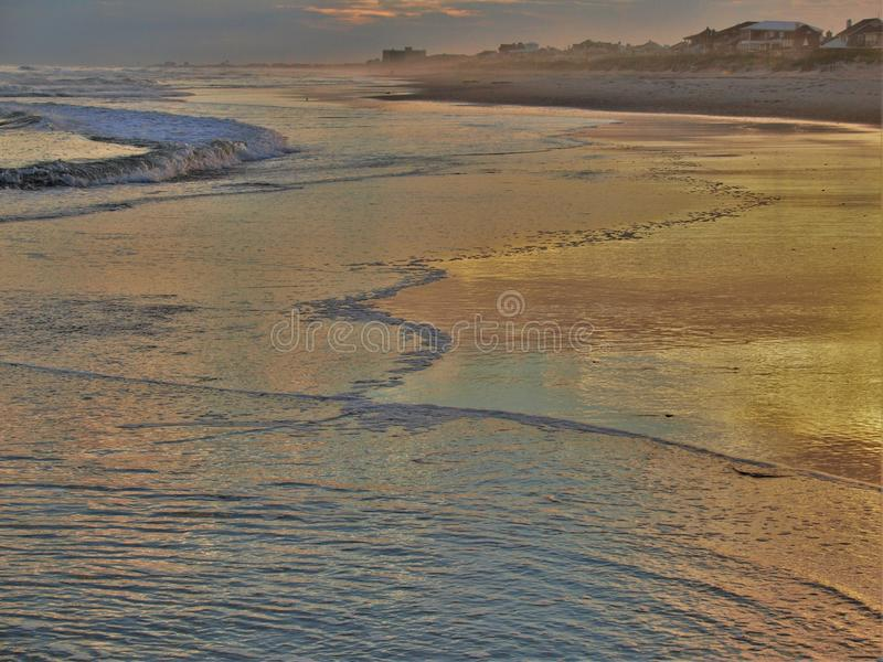 Atlantic Beach Sunset. Setting sun reflects off of the water and sand in Atlantic Beach, North Carolina royalty free stock images