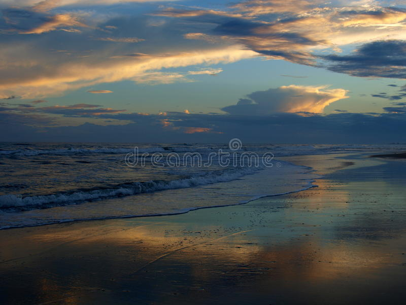 Atlantic Beach Sunset. Setting sun shines off of clouds and reflects off the sand and waves in Atlantic Beach, North Carolina royalty free stock photo