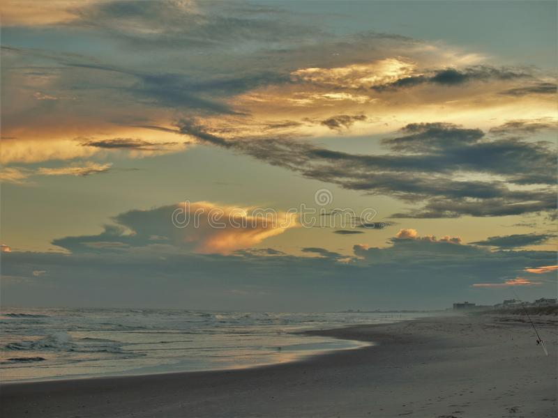 Atlantic Beach Sunset. Setting sun shines off of clouds and reflects off the sand and waves in Atlantic Beach, North Carolina stock image