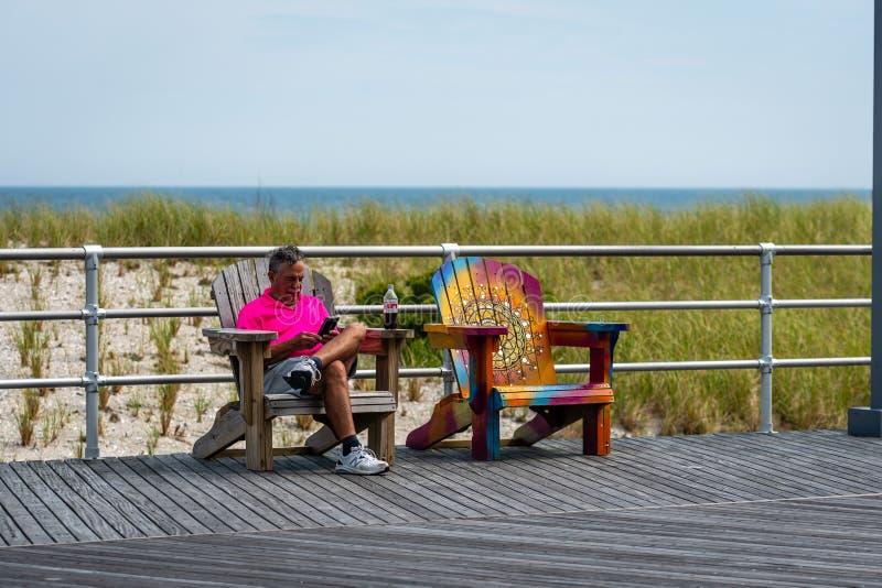 ATLANTIC CITY, NEW-JERSEY - 18 DE JUNHO DE 2019: Um homem que descansa em um banco na borda de um passeio à beira mar de madeira imagens de stock royalty free